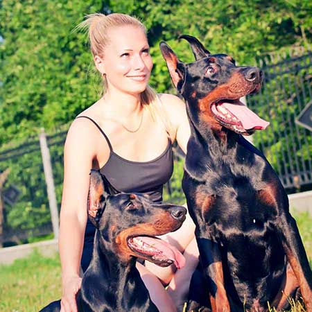 Blonde woman with two Doberman Pinschers
